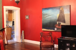 The door on the left leads into the kitchen. Painting by me and a chair that is so ridiculously ornate I had to buy it.